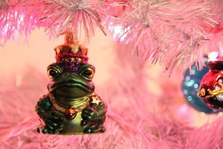 photo of a glass frog ornament hanging in a silver Christmas tree with pink lights
