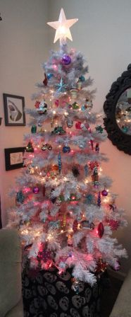 Photo of a silver Christmas tree with white and hot pink lights and brightly colored ornaments