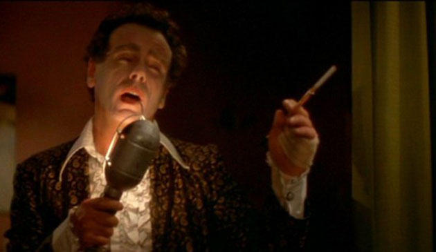 Still from David Lynch movie Blue Velvet, with actor Dean Stockwell singing into a microphone and smoking a cigarette.