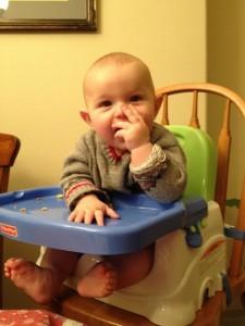 Gabe in his high chair eating Cheerios.