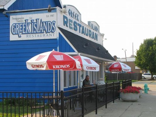 Exterior shot of Greek Islands Restaurant in Indianapolis, Indiana. Building is bright blue, with a sign written in a Greek-esque font. Several tables with red and white umbrellas are on the sidewalk in front of the restaurant.