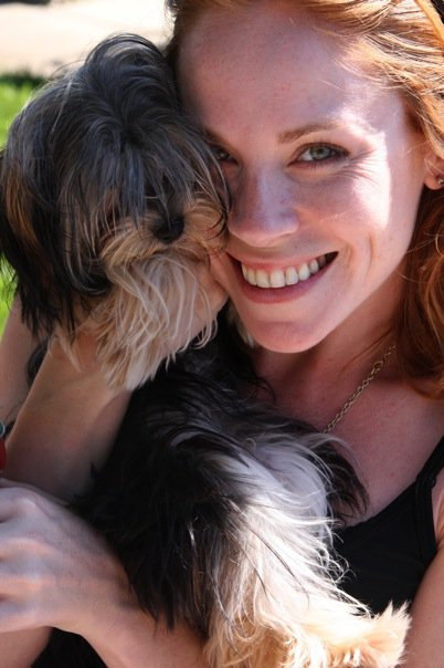 Photo of red headed woman holding a yorkie with long hair covering its eyes