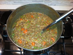 A pot of lamb and lentil stew cooking on the stove.