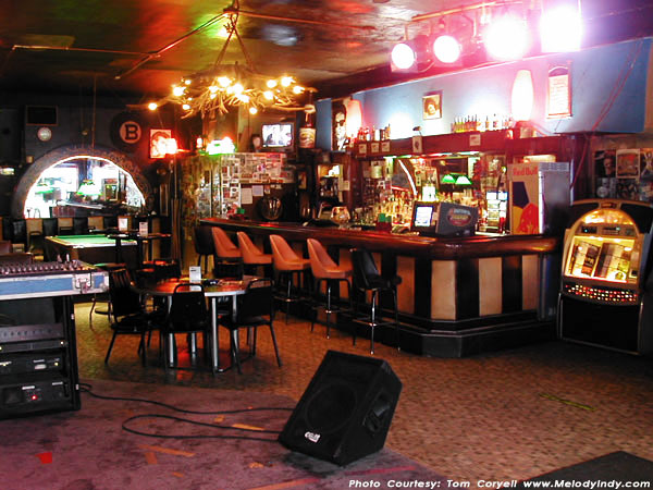Interior shot of brightly decorated dive bar, with a jukebox, a long wooden bar, a hanging lamp made of antlers and a pool table.