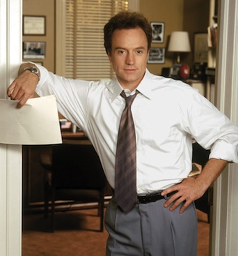 a man with a white shirt and tie leaning in the doorframe of an office. he has a piece of paper in his hand and you can see a desk behind him.