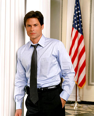 a man in a dress shirt with a tie leaning against a wall. an american flag is in the background.