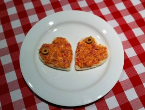 Beef, peanuts, and cheese (among other things) spread on pieces of white bread in the shape of hearts.