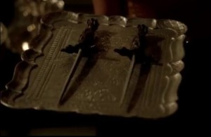 Close up of two daggers on a silver serving tray