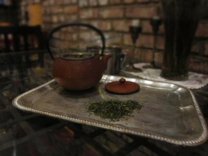 ceramic teapot on a metal tea tray with a small pile of green tea