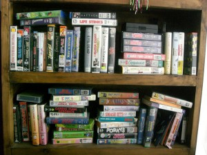 a messy bookcase filled with VHS tapes