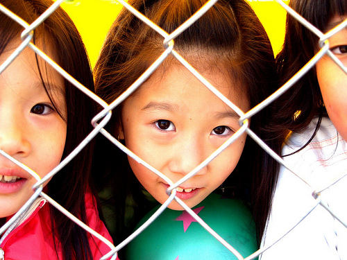 A girl hugs a green ball while standing behind a chain link fence.