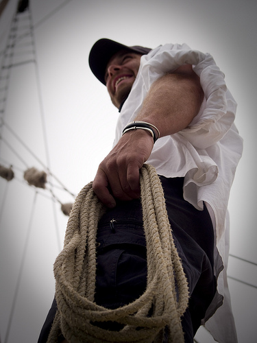 A man holds a rope in his hand and smiles while looking into the distance.