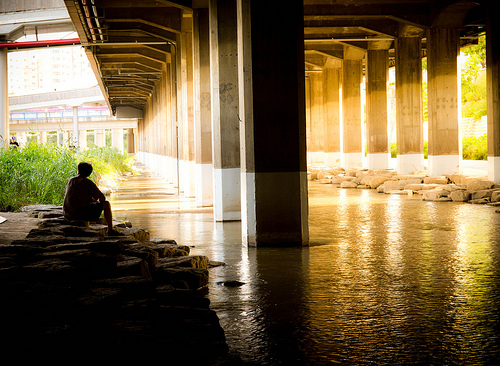 Light illuminates a man resting under a bridge next to a run-off stream.