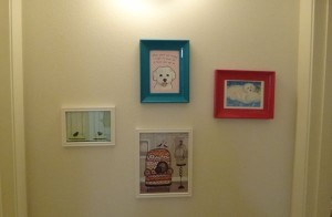 A wall with four framed pictures