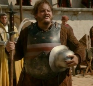 Upper-torso shot of Ser Dontos, holding his helmet and a mace.