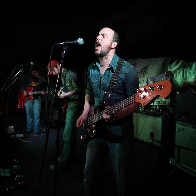 Starkly-lit photo of a bass guitarist singing