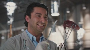 A screencap from the tv show Bones of the character Arastoo holding a disembodied tongue, smiling from ear to ear.