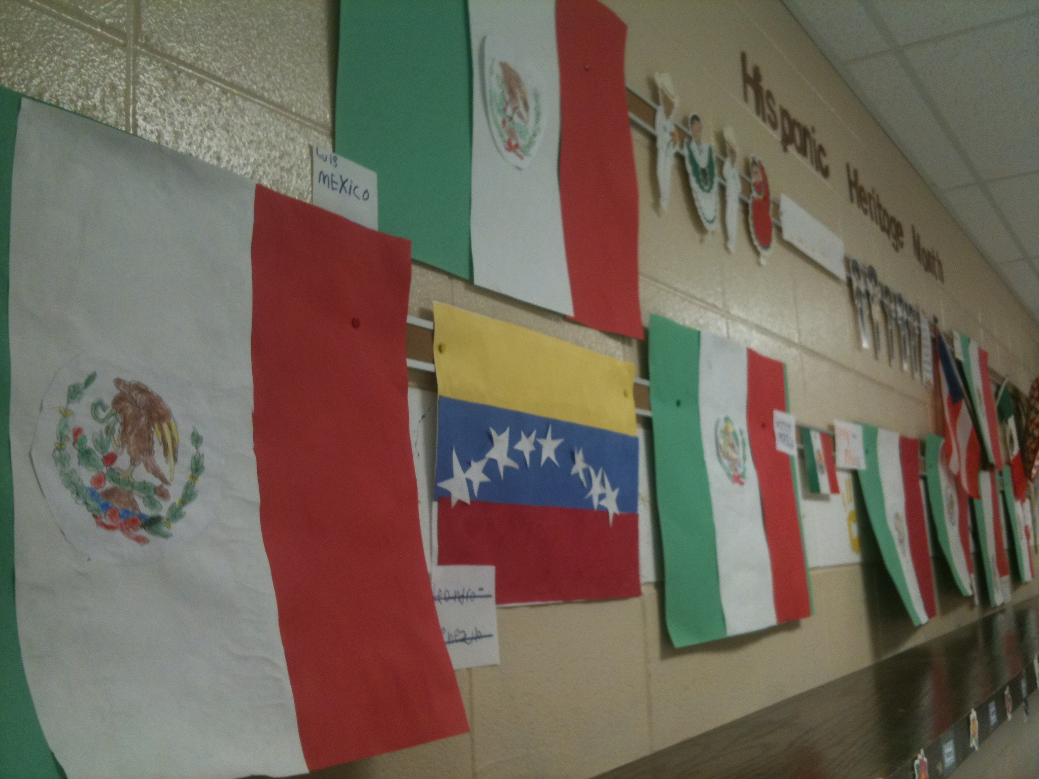 A hallway outside of a bilingual classroom, celebrating Hispanic Heritage Month.  There are student made flags of Mexico and Venezuela.