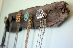 Vintage drawer pulls screwed into old piece of wood with necklaces hanging from it