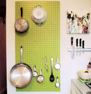 Peg board kitchen storage idea- Painted peg board with hooks used to store pots, pans and utensils in the kitchen