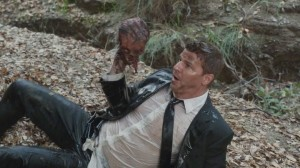 A screencap from an episode of the TV show Bones: The character of Booth, after falling in a stream, holds up a disembodied head