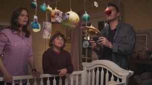 A screencap from the TV show Bones: The characters of Brennan, Parker, and Booth stand around a crib, looking at a homemade mobile