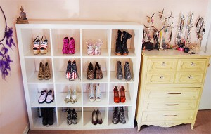 White Ikea Expedit shelf used to display multiple pairs of shoes in a bedroom