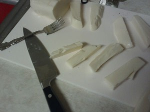 Mozzarella cheese, cut into strips on a white cutting board.