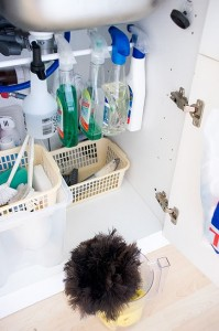 Cleaning supplies hanging from tension rod underneath sink with baskets to hold products below