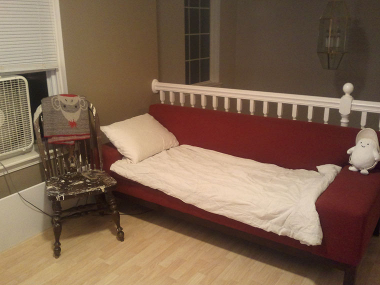 red couch draped with a white blanket