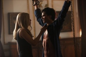 Damon chained up (against his will) as Rebekah drains him of blood.
