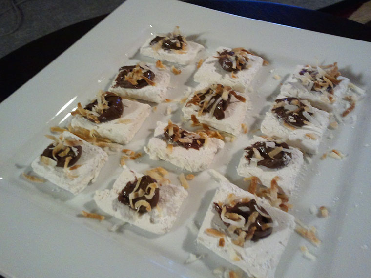 Square white plate with twelve Nutella coconut marshmallows.
