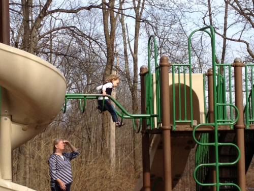 small child on top of monkey bars with unknown woman watching her from below