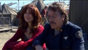 Laura Roslin, in a pretty red dress, sits next to Adama on New Caprica.