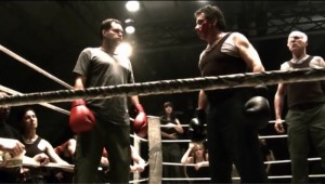 Tyrol and Adama stand in the middle of a boxing ring, glaring at each other .
