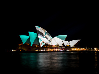 The Sydney Opera House with green, white, and grey designs projected onto the sails.