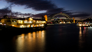 A boat with lights on it sits infront of a lit up bridge under a greying sky.