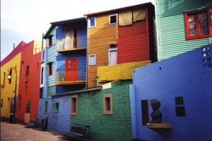 Photo of La Boca neighborhood in Buenos Aires. Homes are painted in vivid shades of blue, red, orange, yellow, and green
