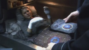 Starbuck lies in her bunk, wearing socks on her bandaged and burned hands. Helo, in the foreground, holds two photographs - one of the Eye of Jupiter, the other of a painting Starbuck did. They're virtually identical.