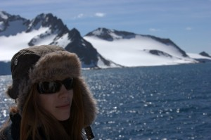 Kym in furry hat in front of mountains and clear blue sky