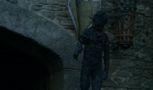 Close up of a burnt child's body handing beside the gate of Winterfell