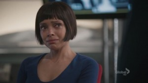 A screenshot from the TV show Bones. The character Cam looks very sad