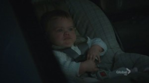 A screenshot from the TV show Bones: a baby in a car seat looks very sad