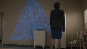 A screenshot from the TV show Bones. A hidden message glows in blue code on a wall