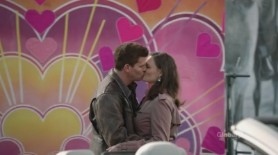 A screenshot from the show Bones: Booth and Brennan kiss in front of a bright, happy backdrop