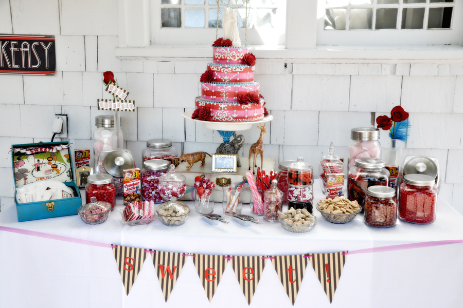candy table with red and pink cake, triangle banner, various jars of multicolored candy and treats