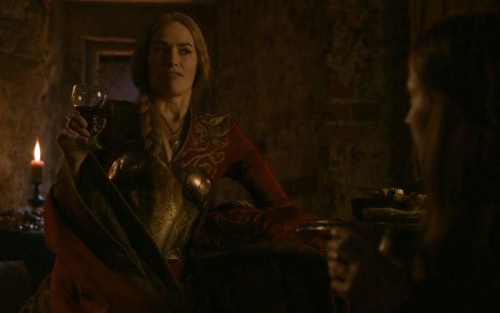 Cersei talks to Sansa, gesturing with her wine glass