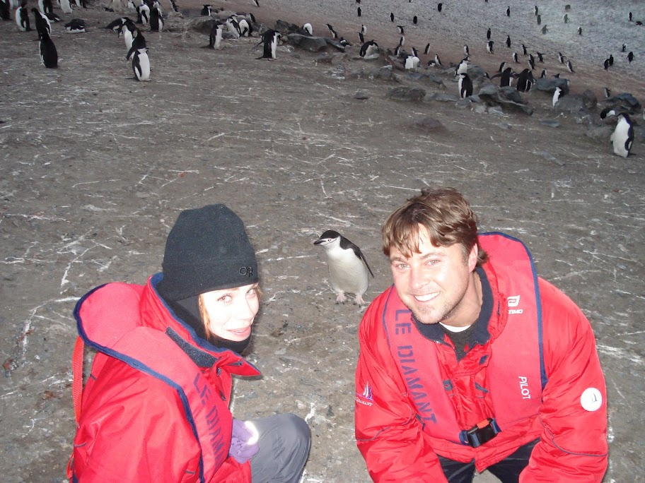 Kym and Mark kneeling in front of curious penguin