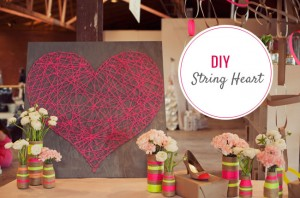 "picture of a red string heart on brown wood background, with a ""DIY String Heart"" sticker, plus some flowers in beige and colored vases"