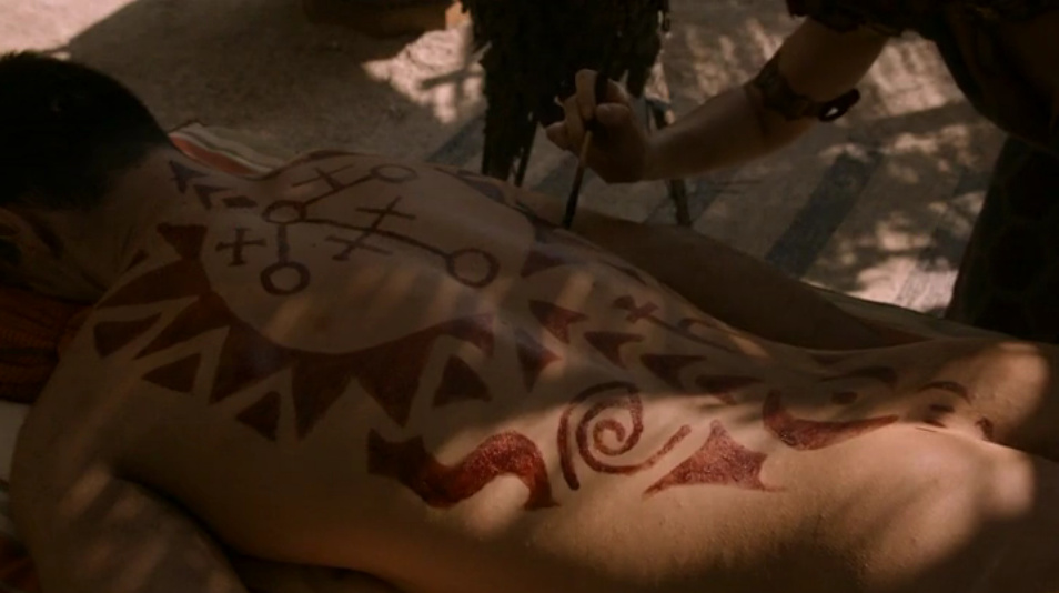 Close up of the markings she is painting on the naked guy